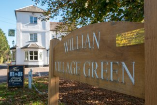 Sign welcoming people to Willian Village green