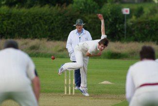 Bowler delivers the ball in a game of cricket
