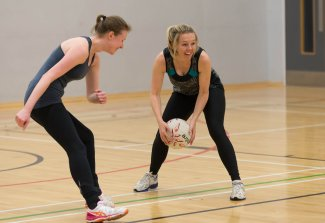 Two ladies playing netball