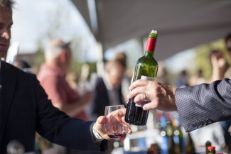 Men taste red wine at a festival
