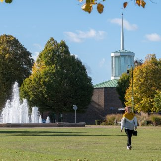 Person walking across Broadway Gardens towards the fountains