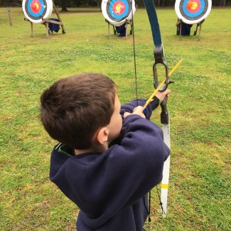 Boy aiming a bow and arrow