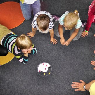 Playgroup of children sit around a toy