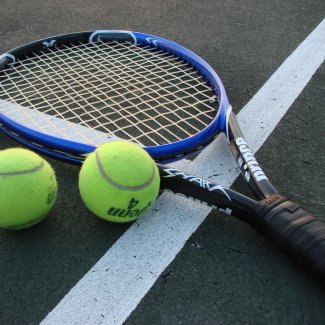 Tennis racket and two ball lie in a tennis court