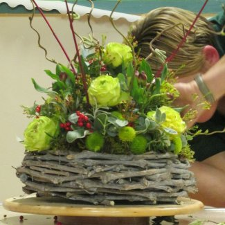 A florest working on a circular flower arrangement