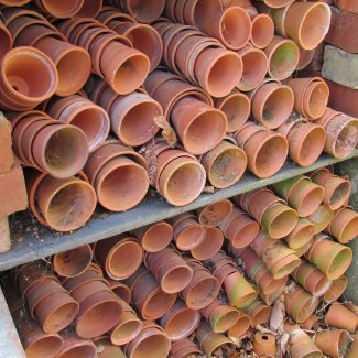 Many terracotta pots stacked on their sides in storage